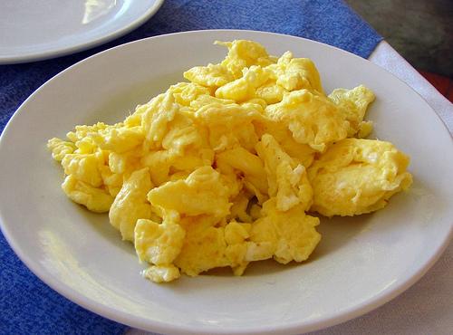 Huevos revueltos que miran los pechos